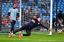 Manchester City goalkeeper Ederson warms up before the game watched by goalkeeper Claudio Bravo