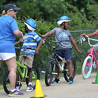 Aubrey Berry, 7, right, catches up with other riders before continuing on with the CATCH Kids bike rodeo Thursday.