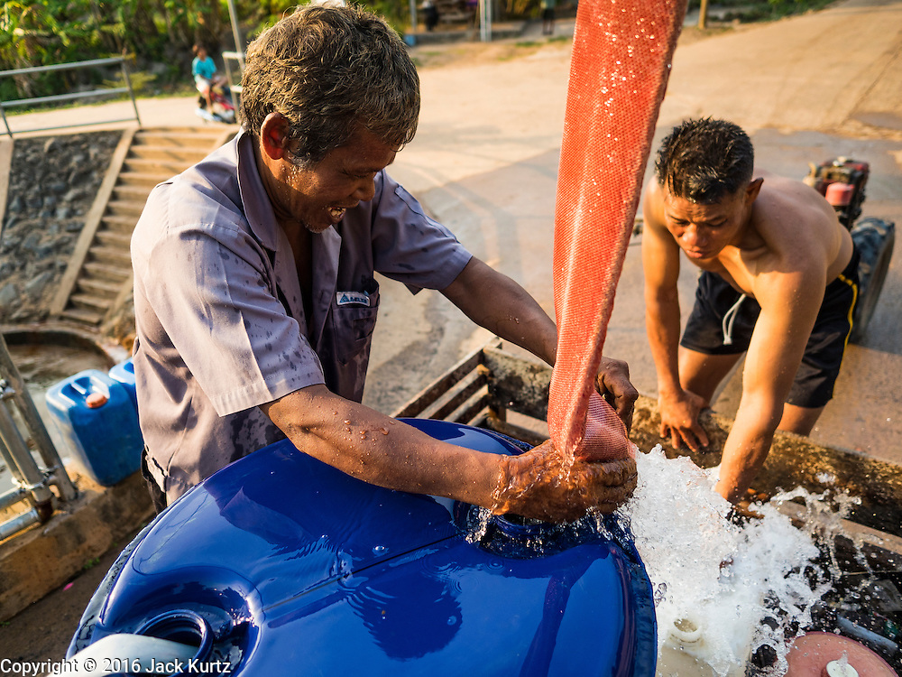 10 MAY 2016 - TA TUM, SURIN, THAILAND:    Men fill barrels of water from the artesian well in Ta Tum, Surin, Thailand. The well is the most important source of drinking water for thousands of people in the communities surrounding it.  In the past many of the people had domestic water piped to their homes or from wells in their villages but those water sources have dried up because of the drought in Thailand. Thailand is in the midst of its worst drought in more than 50 years. The government has asked farmers to delay planting their rice until the rains start, which is expected to be in June. The drought is expected to cut Thai rice production and limit exports of Thai rice. The drought, caused by a very strong El Nino weather pattern is cutting production in the world's top three rice exporting countries:  India, Thailand and Vietnam. Rice prices in markets in Thailand and neighboring Cambodia are starting to creep up.   PHOTO BY JACK KURTZ