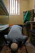 A Muslin prisoner prays on his matt inside his cell at Wandsworth prison..HMP Wandsworth in South West London was built in 1851 and is one of the largest prisons in Western Europe. It has a capacity of 1456 prisoners.