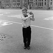 A boy in a playground pointing a gun at his head