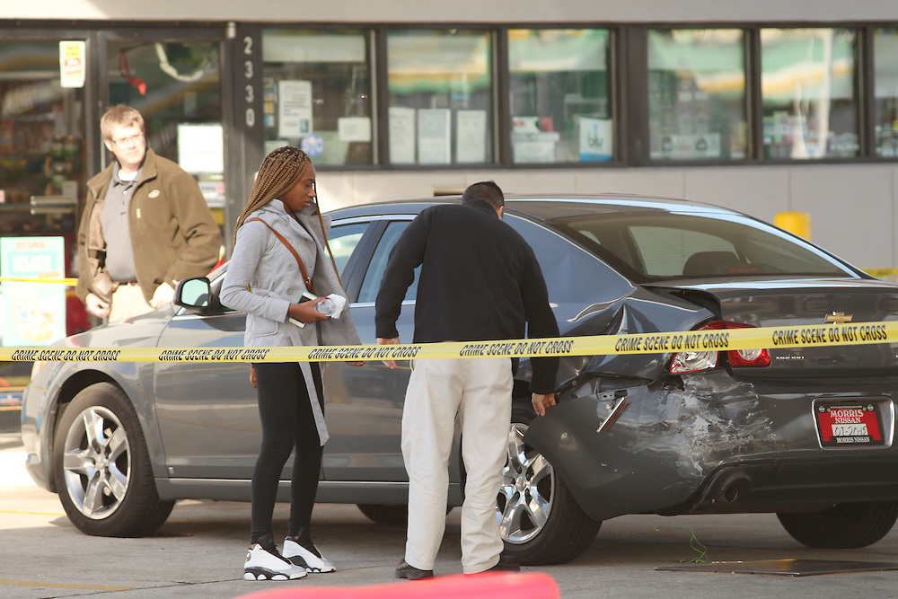 Police investigators inspect a woman's damaged car outside the Exxon gas station at 2330 Ashley Phosphate Road in North Charleston where a man was fatally shot Friday. (ANDREW KNAPP/STAFF)