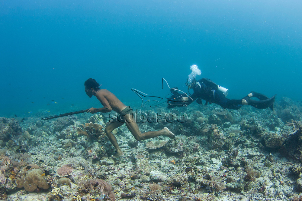 Sulbin, a Bajau sea gypsy spearfisherman freediving and walking on the seabed hunting for fish on the coral reef, being filmed by cameraman Roger Munns, Mabul Island, Sabah, Malaysia.