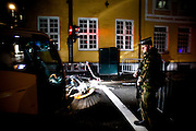 Oslo, Norway, 24.07.2011. Army soldiers are controlling identification of workiers entering the governmental area of the city. Late at night, Oslo is quiet though packed with people. They are all quiet, walking with flowers in their hands towards Domkirken, the main cathedral in Oslo. Oslo awakes to shocking messages of the total bodycount after yesterdays massacre. A total of 91 persons were killed in the massacre in Utøya right outside Oslo. Seven of those died when a car bomb was detonated outside the main government biuilding in the heart of Oslo, friday 22. of July. Foto: Christopher Olssøn.
