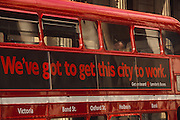"A male passenger is asleep with his mouth open, leaning his head on a bus window as it passes the background pillars of the Bank of England in the financial district City of London. On the exterior of the bus are the words: ""We've got to get this city to work,"" an advertising slogan used by London Transport to seduce commuters from their cars and back on to public transport which is one of the most expensive world capitals on which to travel by bus, train or underground. This style of bus is a traditional design called a 'Routemaster' which has been in service on the capital's roads since 1954 and is nowadays only seen on heritage routes such as these destination: Victoria, Bond Street, Oxford Street, Holborn and Bank (the Bank of England). From any angle, the bus is easily recognisable as that classic British transport icon.  The City of London has a resident population of under 10,000 but a daily working population of 311,000. The City of London is a geographically-small City within Greater London, England. The City as it is known, is the historic core of London from which, along with Westminster, the modern conurbation grew. The City's boundaries have remained constant since the Middle Ages but  it is now only a tiny part of Greater London. The City of London is a major financial centre, often referred to as just the City or as the Square Mile, as it is approximately one square mile (2.6 km) in area. London Bridge's history stretches back to the first crossing over Roman Londinium, close to this site and subsequent wooden and stone bridges have helped modern London become a financial success."