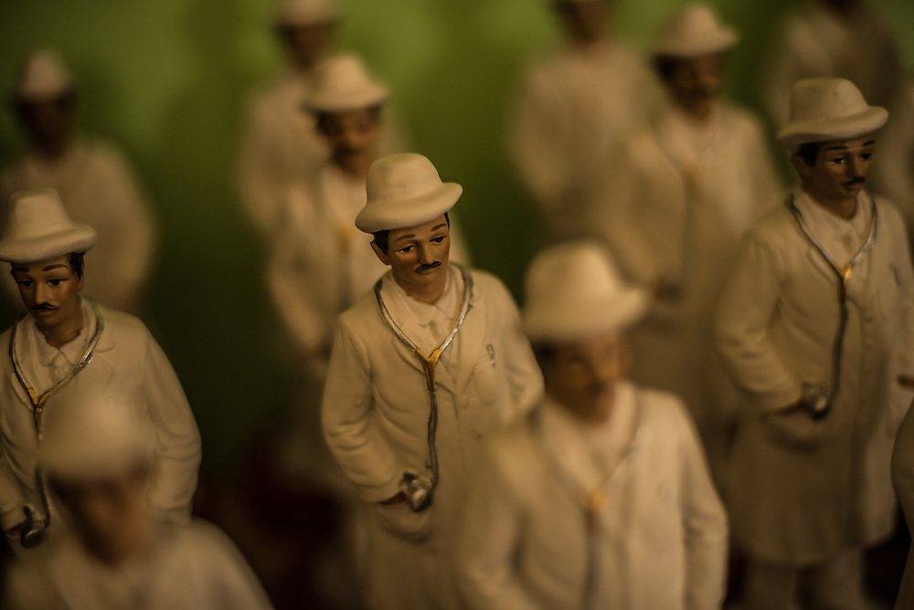 "ISNOTÚ, VENEZUELA - AUGUST 26, 2014: Figurines of Dr. José Gregorio Hernández for sale in the gift shop. Hundreds and often thousands of pilgrims arrive every day to Isnotú, Venezuela to pay tribute to Dr. José Gregorio Hernández, one of the country's most popular folk heroes, at a large shrine that has become the town's main attraction.The Catholic church in Venezuela is on a crusade to document a miracle that can be attributed to the  medical doctor, born 150 years ago, and who is revered for being the ""doctor of the poor"". PHOTO: Meridith Kohut for The New York Times"