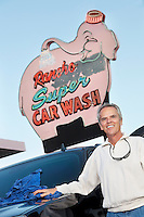 Portrait of mature owner of car wash standing below signboard with vehicle
