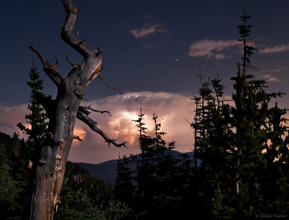 Lightning illuminates a distant thunderstorm while the moon illuminates the landscape.