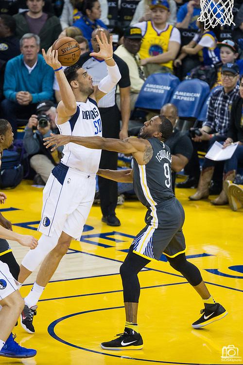 Golden State Warriors forward Andre Iguodala (9) defends Dallas Mavericks center Salah Mejri (50) at Oracle Arena in Oakland, California, on February 8, 2018. (Stan Olszewski/Special to S.F. Examiner)