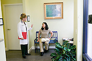 Female doctor greeting female patient in the lobby of a medical office, Tucson, Arizona..Media Usage:.Subject photograph(s) are copyrighted Edward McCain. All rights are reserved except those specifically granted by McCain Photography in writing...McCain Photography.211 S 4th Avenue.Tucson, AZ 85701-2103.(520) 623-1998.mobile: (520) 990-0999.fax: (520) 623-1190.http://www.mccainphoto.com.edward@mccainphoto.com