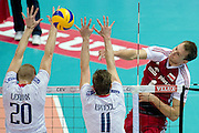 (R) Bartosz Kurek from Poland attacks against (L) Kevin Le Roux and (C) Julien Lyneel both from France during the 2013 CEV VELUX Volleyball European Championship match between Poland and France at Ergo Arena in Gdansk on September 21, 2013.<br /> <br /> Poland, Gdansk, September 21, 2013<br /> <br /> Picture also available in RAW (NEF) or TIFF format on special request.<br /> <br /> For editorial use only. Any commercial or promotional use requires permission.<br /> <br /> Mandatory credit:<br /> Photo by &copy; Adam Nurkiewicz / Mediasport