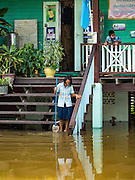 30 SEPTEMBER 2016 - SAI NOI, AYUTTHAYA, THAILAND: A student at Wat Boonkannawas School clean up the flood waters that have inundated the school. The Chao Phraya River, the largest river that runs through central Thailand, has hit flood stage in several areas in Ayutthaya and Ang Thong provinces. Villages along the river are flooded and farms are losing their crops due to the flood. This is the same area that was devastated by floods in 2011, but the floods this year are not expected to be as severe. The floods are being fed by water released from upstream dams. The water is being released to make room for heavy rains expected in October.      PHOTO BY JACK KURTZ