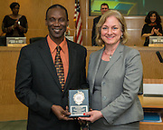 Sherrie Robinson, right, presents Femi Afolayan, left, with the Houston ISD Employee of the Month award during the Board of Education meeting, October 9, 2014.