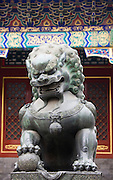 Statue of a bronze male lion with paw on a ball at The Summer Palace, Beijing, China