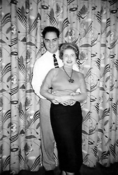 1950's photograph of a couple embracing indoors by a curtain