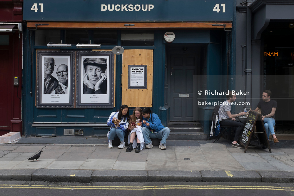 With a further 89 UK covid victims in the last 24hrs, bringing the total victims to 43,995 during the Coronavirus pandemic, pubs, restaurants and hairdressers will be able to reopen on 4th July, providing they adhere to COVID Secure guidelines. The Ducksoup dining room remains closed and Londoners sit outside while bar customers sit alongside on Dean Street in Soho, on 2nd July 2020, in London, England.