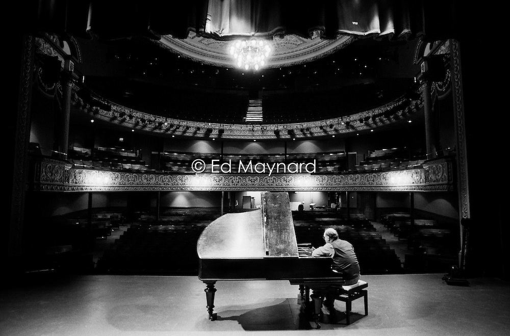 Piano tuner Paul Chrimes, a member of the Association of Blind Piano Tuners, working on a grand piano on the stage of the Grand Theatre, Wolverhampton, England, UK.