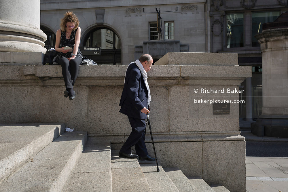 Using walking sticks, an elderly gentleman gently walks down the steps of Royal Exchange at Bank Triangle, on 10th May 2017, in the City of London, England.