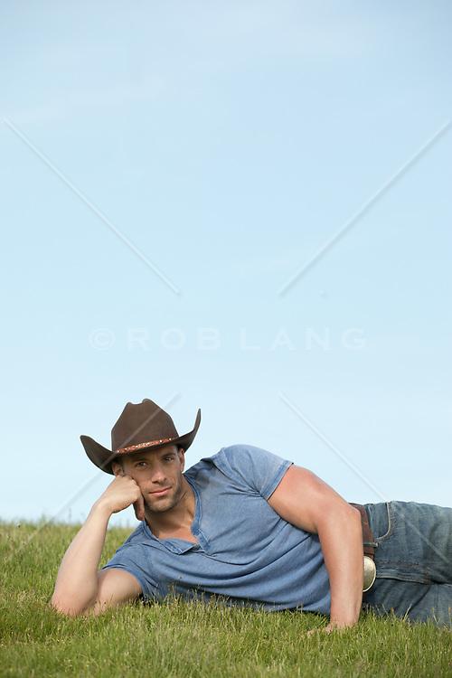 hot cowboy relaxing on a grassy hillside