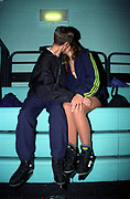 A couple wearing ice skates kissing at an ice rink, UK, 2000's