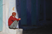 A man crouching by a wall in the medina or old town of Chefchaouen in the Rif mountains of North West Morocco. Chefchaouen was founded in 1471 by Moulay Ali Ben Moussa Ben Rashid El Alami to house the muslims expelled from Andalusia. It is famous for its blue painted houses, originated by the Jewish community, and is listed by UNESCO under the Intangible Cultural Heritage of Humanity. Picture by Manuel Cohen