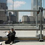 USA - New York - 05-05-2005<br /> World Trade centre , groud zero , de plek waar de Twin towers stonden.<br /> De grote bouwput , is nu bouwrijp voor een nieuw gebouwen complex.<br /> Een zwerver probeert geld te vedienen met een fluit.<br /> Foto: Sake Elzinga