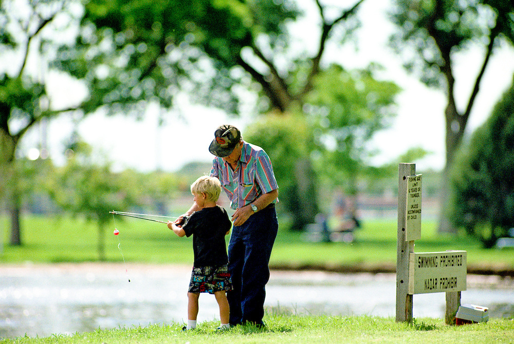 A grandfather helps his grandson son cast his line at a small pond in Colorado.