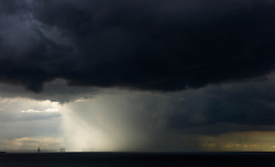 © Licensed to London News Pictures. <br /> 10/06/2014. <br /> <br /> Saltburn, United Kingdom.<br /> <br /> Dark thunder clouds and a rain squall form out at sea on Teesside. <br /> <br /> Photo credit : Ian Forsyth/LNP