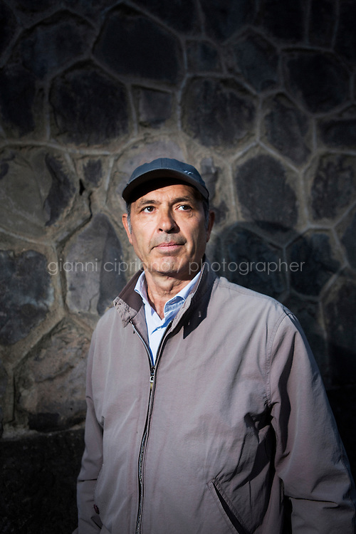 """NAPOLI, ITALY - 8 OCTOBER 2016: Pietro Ioia (57), activist and president of the association Ex D.O.N. (ex detenuti organizzati napoletani - organized ex Napoletan prisoners) and former drug trafficker for the Camorra, poses for a portrait in front of the prison of Poggioreale in Napoli, Italy, on October 8th 2016. Pietro Ioia was a drug trafficker for the Camorra, the Italian Mafia-type crime organization which arose in the region of Campania and its capital Naples. For his crimes, he spent 22 years in prison. After being released, Mr. Ioia founded the association Ex D.O.N. (ex detenuti organizzati napoletani - organized ex Napoletan prisoners) which focuses on prisoners' rehabilitation in society after being released. Pietro Ioia also denounces prison guards abuses withing the Naples prison of Poggioreale. He publicly denounced the existence of the """"Cella Zero"""" (Cell Zero), an unnumbered cell inside the prison of Poggioreale, Naples, where prisoners were illegally beaten by prison guards."""