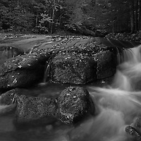 This intimate black and white landscape photography image of Flume Brook at Franconia Notch State Park near Lincoln in the New Hampshire White Mountains region features silky water tumbling down the creek during New England fall foliage season. Table Rock is a small section of Conway granite in this New Hampshire State Park that was exposed and outcropped of hundreds of years. This scenic New Hampshire cascading water section is 500 feet long and 75 feet wide.<br /> <br /> This NH B&amp;W landscape photography image is available as museum quality photography prints, canvas prints, acrylic prints or metal prints. Black and white photography fine art prints may be framed and matted to the individual liking and decorating needs:<br /> <br /> http://juergen-roth.pixels.com/featured/new-hampshire-table-rock-nature-juergen-roth.html<br /> <br /> All photographs are available for digital and print image licensing at www.RothGalleries.com. Please contact me direct with any questions or request.<br /> <br /> Good light and happy photo making!<br /> <br /> My best,<br /> <br /> Juergen<br /> Prints: http://www.rothgalleries.com<br /> Photo Blog: http://whereintheworldisjuergen.blogspot.com<br /> Twitter: @NatureFineArt<br /> Instagram: https://www.instagram.com/rothgalleries<br /> Facebook: https://www.facebook.com/naturefineart