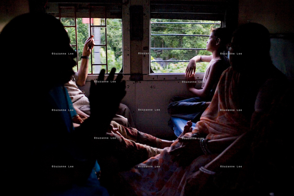 10 year old Ritik Goswami looks out the windows at the palm and coconut trees of Kerala as his mother and her friends sing self-composed Hindu devotional songs on the Himsagar Express 6318 on 9th July 2009.. .6318 / Himsagar Express, India's longest single train journey, spanning 3720 kms, going from the mountains (Hima) to the seas (Sagar), from Jammu and Kashmir state of the Indian Himalayas to Kanyakumari, which is the southern most tip of India...Photo by Suzanne Lee / for The National