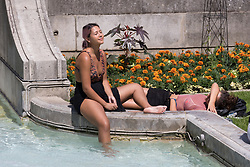 © Licensed to London News Pictures. 07/07/2017. LONDON, UK.  Emily Grace and her friend relax next to a fountain at lunchtime near St Paul's Cathedral in London during hot and sunny weather today.  Photo credit: Vickie Flores/LNP