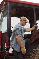 farmer getting on a tractor