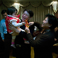 BEIJING, 25. JANUARY, 2009 :   Mr. Li's  grandchild receives a &quot;hongbao&quot; ( red envelope) from relatives  on new years' eve  in Beijing .<br /> Mr. Li, a paper factory owner, is facing one of his most difficult times .&quot; Last November the market suddenly went down ,&quot; Li says.   <br /> He had bought paper, a lot of paper, and paid 7000 Yuan/ t .<br />  Li's company buys paper from paper mills and lives from the sales to publishing houses and other companies.  Since the market's collapse , he manages to sell the paper only for 6000 Yuan/t.<br /> His clients' export business to the USA had shrunk in Southern China. Mobile phone manufacturers don't need paper for the instruction guides to their mobile phones anymore as their US clients buys less China- made mobile phones.<br />  Toy manufacturers don't need paper anymore  because Americans import less toys from China. &quot; The crisis has driven many of my clients into bancruptsy&quot;, says Li.<br />  <br /> China's Communist Party  which will celebrate its 60th anniversary in October, currently faces its biggest challenge since the beginning of the economic reforms 30 years ago  : &quot; The phase of  rapid economic growth is over. For the first time the government is threatened with a  mistrust of a wide section of the population&quot;, warns the Communist party's Shang Dewen in Beijing.   <br /> Not only the China's poorest worry about the furture, but as well China's middle class is concerned about the crisis.     1,5 Millionen university graduates didn't find a job until the end of 2008  and this summer there'll be an additional  6,1 Million new graduates. More than 12 percent of university graduates face unemployment in 2009.