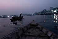 A small canoe lanched from Sadarghat boat terminal makes it's way through the Buriganga River in Dhaka, Bangladesh, at dusk.