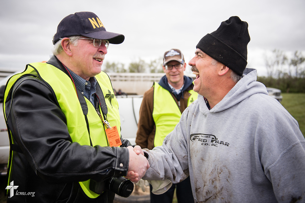 The retiring South Dakota District President Rev. Dr. Dale Sattgast shakes hands with the treasurer of Zion Lutheran Church at his destroyed farm on Monday, May 11, 2015, in Delmont, S.D. A tornado swept through the area the previous day and destroyed Zion Lutheran Church and nearby buildings. Behind Sattgast is the newly elected South Dakota District President Rev. Scott Sailer of Sioux Falls. LCMS Communications/Erik M. Lunsford
