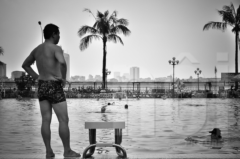 A man is standing up next to a diving board in front of the Sao Mai swimming-pool in Hanoi, after the rain.  There is West lake in the background and palm trees.
