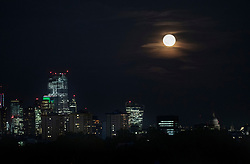 © Licensed to London News Pictures. 15/08/2019. London, UK. Cloud partially covers the Sturgeon full moon as it rises over central London. The August full moon is known as the Sturgeon Moon because native American indians believed that the sturgeon fish could most easily be caught at that time. Photo credit: Peter Macdiarmid/LNP