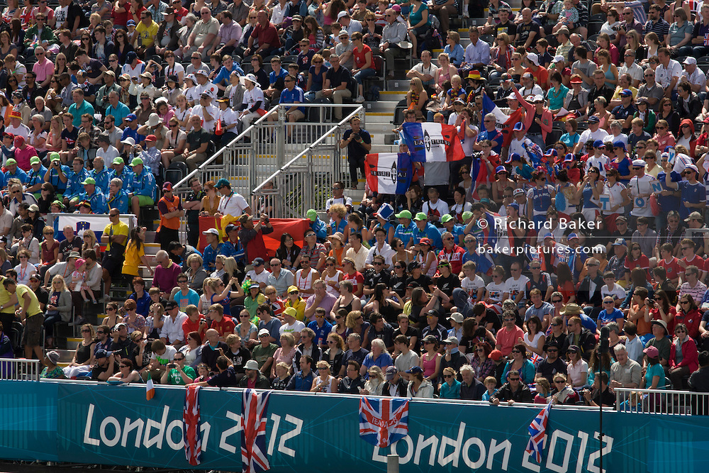 French fans hold up their national flags surrounded by crowds of sports supporters seem en mass during the canoe slalom heats at the Lee Valley White Water Centre, north east London, on day 3 of the London 2012 Olympic Games.