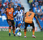 Brighton midfielder winger Kazenga LuaLua exploits the gap between Hull City midfielder Tom Huddlestone and Hull City midfielder Moses Odubajo during the Sky Bet Championship match between Brighton and Hove Albion and Hull City at the American Express Community Stadium, Brighton and Hove, England on 12 September 2015. Photo by Bennett Dean.