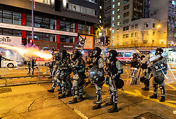 Hong Kong. 6 October 2019. Tens of thousands of pro-democracy protestors march in pouring rain through centre of Hong Kong today from Causeway Bay to Central. Peaceful march later turned violent as a hard-core of protestors confronted police. Pic; Riot police fire tear gas in Causeway Bay. Iain Masterton/Alamy Live News.
