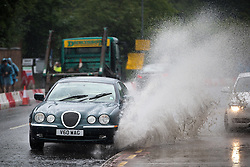 © Licensed to London News Pictures . 11/06/2016 . Manchester , UK . A Jaguar is driven through thick standing water on Bury Old Road in North Manchester following heavy rain . Photo credit : Joel Goodman/LNP