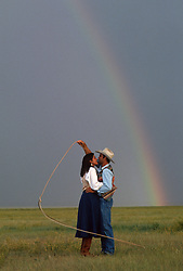 Cowboy with a lasso and girl with a rainbow in the sky