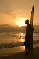 Surfer standing on beach leaning on surfboard watching sunset side view