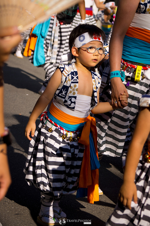 A boy holding his mother's hand in the parade of the Tenjin Festival (Tenjin Matsuri) in Osaka.
