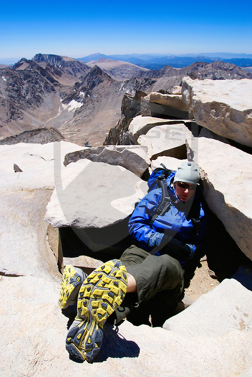 hiker resting with feet kicked back on the summit of mount whitney in the high sierra nevada mountain landscape of california.
