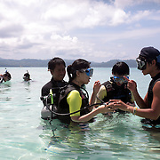 Asian tourists during a scuba diving lesson in the ocean at White Beach,  Boracay Island, the Philippines on October 3, 2008, Photo Tim Clayton..Asian tourists at White Beach, Boracay Island, the Philippines...The 4 km stretch of White beach on Boracay Island, the Philippines has been honoured as the best leisure destination in Asia beating popular destinations such as Bali in Indonesia and Sanya in China in a recent survey conducted by an International Travel Magazine with 2.2 million viewers taking part in the online poll...Last year, close to 600,000 visitors visited Boracay with South Korea providing 128,909 visitors followed by Japan, 35,294, USA, 13,362 and China 12,720...A popular destination for South Korean divers and honeymooners, Boracay is now attracting crowds of tourists from mainland China who are arriving in ever increasing numbers. In Asia, China has already overtaken Japan to become the largest source of outland travelers...Boracay's main attraction is 4 km of pristine powder fine white sand and the crystal clear azure water making it a popular destination for Scuba diving with nearly 20 dive centers along White beach. The stretch of shady palm trees separate the beach from the line of hotels, restaurants, bars and cafes. It's pulsating nightlife with the friendly locals make it increasingly popular with the asian tourists...The Boracay sailing boats provide endless tourist entertainment, particularly during the amazing sunsets when the silhouetted sails provide picture postcard scenes along the shoreline...Boracay Island is situated an hours flight from Manila and it's close proximity to South Korea, China, Taiwan and Japan means it is a growing destination for Asian tourists... By 2010, the island of Boracay expects to have 1,000,000 visitors.