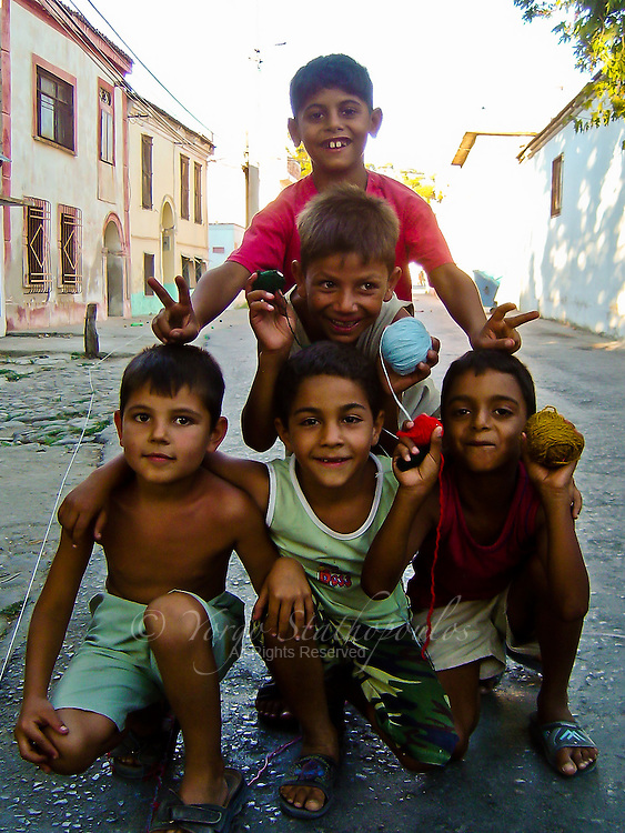 Strolling through the streets of Aivalik, Turkey I found these kids playing with the only thing they could get their hands on; yarn.