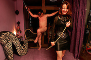 """DOMINATRIX CLUB """"LA SIORA"""" at Shinjuku - Tokyo - Submisive client with Dominatrix Ria  during an S&M session. .La Siora is one of the oldest dominatrix houses in Tokyo, it was conceived xxyears ago and boasts an impressive client base of 4000 slaves, wanting to get whipped for fun. Basically paying clients come here from a variety of backgrounds to indulge in their fantasies at 30000 yen a pop (p/hour)..Rie is the manageress and head dominatrix of the establishment. When we asked her why she ever got into SM, she replies quite simply she thought it looked cool and she likes to try new things. Her specialties are whipping and shibari- Japanese rope bondage which she explains is an art unto itself that requires, months to years of practice and training. Her manner is impeccably polite, and her demeanor is pleasant, which makes her profession all the stranger given her friendly manner."""