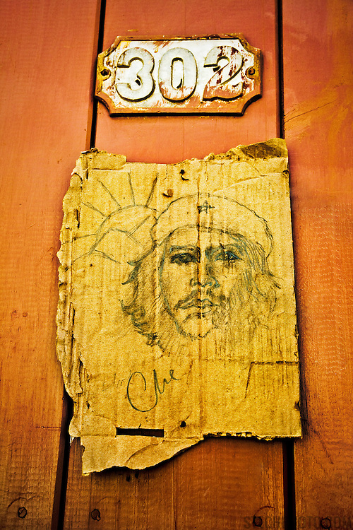 A portrait of Ernesto Che Guevara sketched on a piece of cardboard hanging on a door in the town of Trinidad, Cuba.<br /> <br /> + ART PRINTS +<br /> To order prints or cards of this image, visit:<br /> http://greg-stechishin.artistwebsites.com/featured/1-che-guevara-greg-stechishin.html